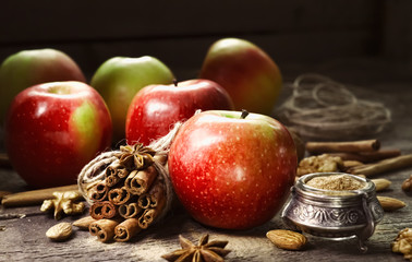 Fresh red and green apples, cinnamon sticks, ground cinnamon, anise stars, walnuts and hazelnuts on an old wooden background