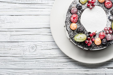 chocolate berry cake on plate over white wooden background