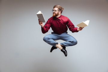 Male nerd jumping and reading in-flight