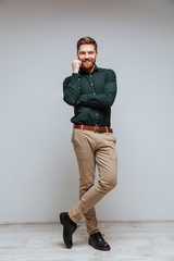 Vertical image of Smiling Bearded man talking on phone