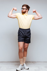 Vertical image of Male nerd showing his biceps