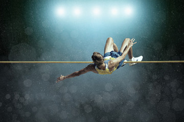 Athlete in action of high jump. Wall mural