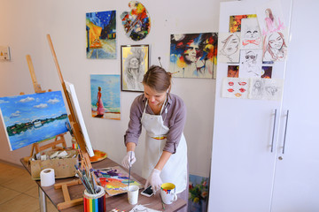 Beautiful young painter paints picture uses brushes and oil, and