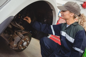 Female mechanic examining a car wheel disc brake