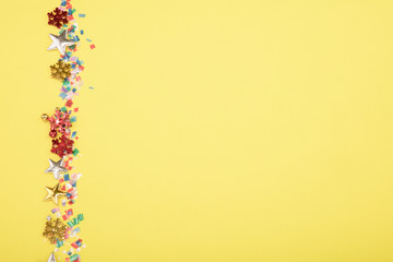 Red, yellow and green heart and circle confetti on a YELOW background. High resolution photo.