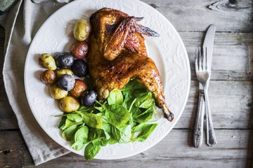 Half a grilled chicken with roast potatoes and spinach (seen from above)
