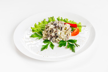 Plate of salad with beef and mushrooms decorated with vegetables isolated at white background.
