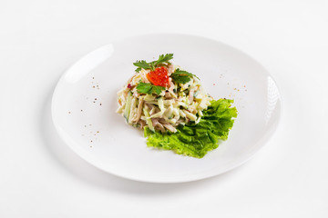 Plate of fresh salad with ham, potato and cucumbers decorated with red caviar isolated at white background.