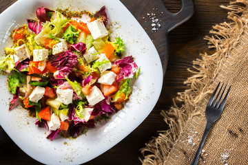 Fresh diet vegeterian salad decorated with herbs on wooden tray at table background.