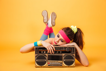 Cute young woman athlete lying and sleeping on retro boombox