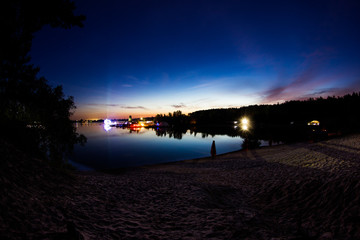 Landscape. Beautiful colorful Sunset with view of lake and forest. Light of music Festival