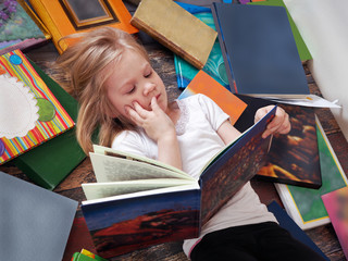 child and a lot of books around. Little girl reading a book lying on the floor