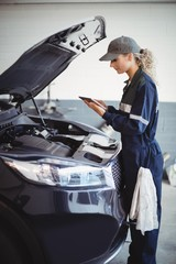 Female mechanic using digital tablet