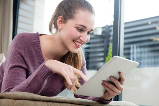 beautiful young woman using a home tablet, low angle view