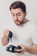photographer cleaning camera with vacuum pump. hand blower dust
