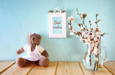 cute teddy bear sitting next to spring cherry tree