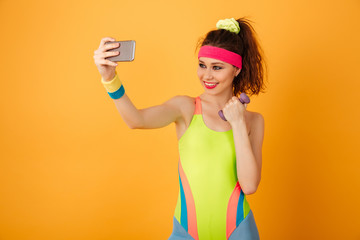 Smiling fitness woman with dumbbell making selfie using cell phone