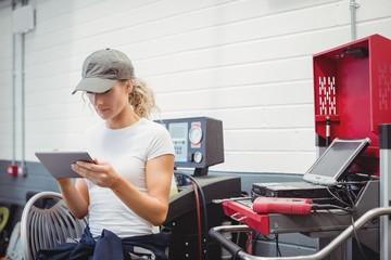 Female mechanic using digital tablet