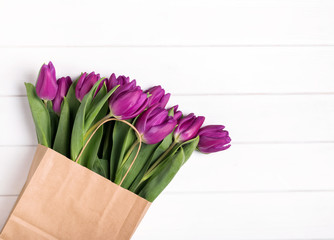 Pink tulips in a paper bag on the white wooden table