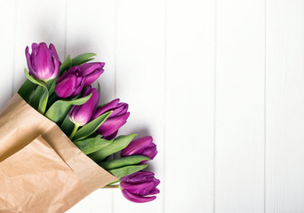 Pink tulips wrapped in craft paper on the white table