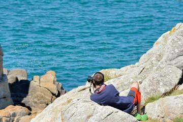 Un homme est allongé sur un rocher pour prendre une photo