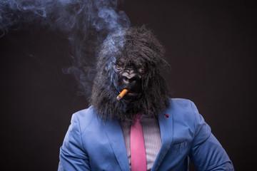 businessman wearing gorilla mask and smoking cigar