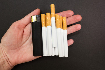 Cigarettes and a lighter in the hand of the woman on a black background