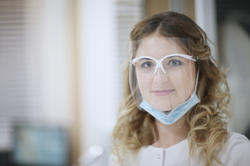 Portrait of a woman dentist in a protective mask in the office of a dental clinic