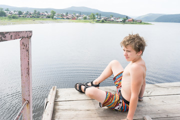 Young boy relaxes on a tower for jumping into the water. Boy resting near the lake. Swimmer in shorts. summer rest. teenager sunbathe on the waterfront
