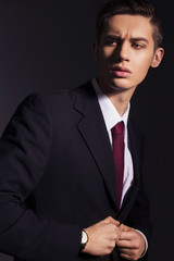 Young handsome men in black suit jacket, white shirt and red tie wear watches looking sideways. dark background. indoors. copy space
