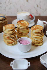 Pancakes with berry sauce on a white plate. Bank of jam and cups in the background. Closeup