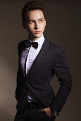 Young handsome brunette macho businessman in black suit and bow tie. neutral background