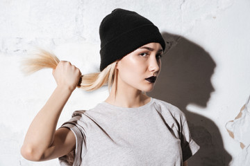 Hipster in black hat holding her hair