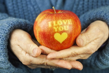 Apple with inscription I love you on old woman's hands