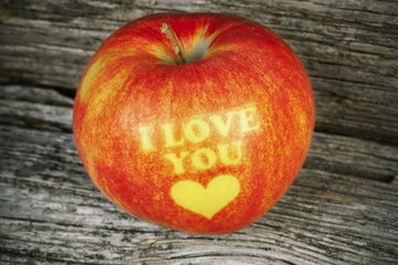 Apple with an inscription I love you on wood