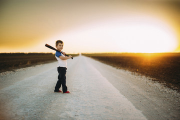Portrait of boy holding baseball bat while standing on road amidst field against sky during sunset