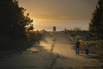 Rear view of boys walking on road against sky during sunset