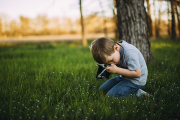 Side view of boy photographing through vintage camera