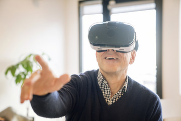 Smiling man pointing while wearing virtual reality simulator at home