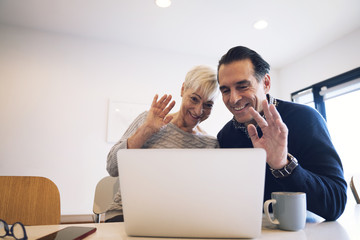 Happy senior couple waving while looking at laptop computer in home