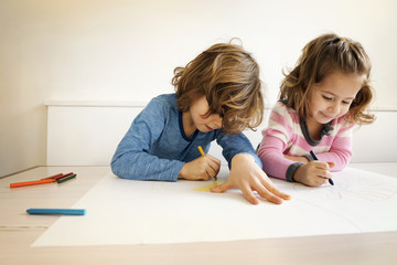 Siblings drawing at table in home