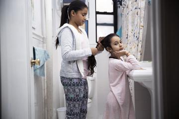 Girl tying hair of sister while standing in bathroom