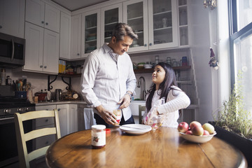 Father looking at girl removing bread from packet while standing in kitchen
