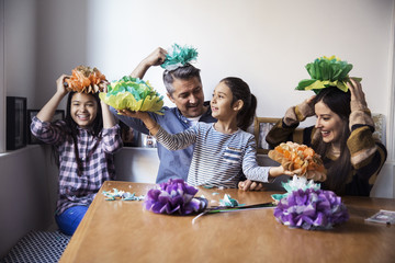Happy family playing with homemade paper flowers while sitting at table