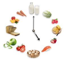 Clock arranged from healthy food products isolated on white background. Healthy food concept.