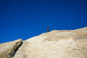Low angle view of hiker walking on mountain against clear blue sky during sunny day