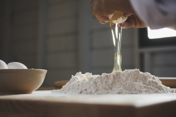 Cropped image of woman breaking egg in flour on table