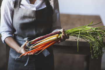 Midsection of woman holding various carrots while standing in kitchen