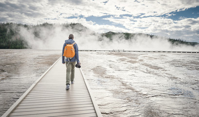 Rear view of man walking on boardwalk amidst lake against cloudy sky