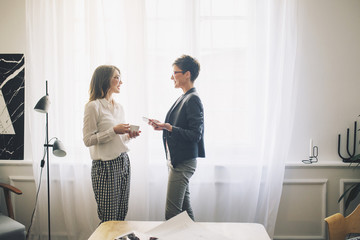 Businesswomen talking while standing by curtain in office
